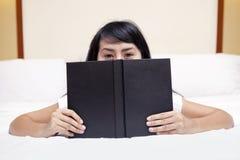 Allievo che dà una occhiata da dietro il libro Fotografie Stock Libere da Diritti
