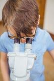 Allievo che guarda tramite il microscopio nella classe Fotografia Stock