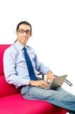 Allievo che lavora con il computer portatile sul sofà Immagini Stock Libere da Diritti