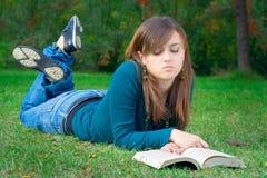 Allievo che legge un libro nella sosta Fotografia Stock
