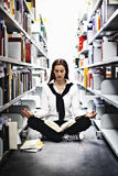 Allievo che meditating sopra un libro in libreria. Fotografia Stock