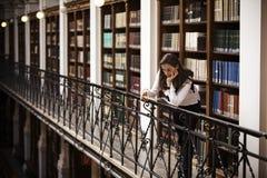 Allievo che si appoggia e che legge nella libreria. Immagini Stock