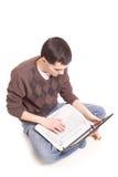 Allievo che si siede con un computer portatile Fotografie Stock