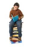Allievo che si siede su un mucchio dei libri Fotografia Stock Libera da Diritti