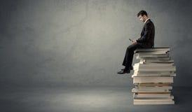 Allievo che si siede sul mucchio dei libri Immagine Stock