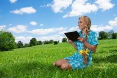 Allievo che si siede sull'erba che passa in rassegna Immagini Stock