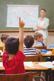 Allievo che solleva mano durante la lezione di geografia nel classrorm Fotografie Stock