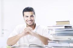 Allievo che sorride con i libri su priorità bassa bianca Fotografia Stock