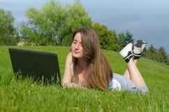 Allievo che studia all'aperto sul suo computer portatile Immagini Stock Libere da Diritti