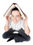 Allievo che tiene un libro sopra la sua testa Fotografia Stock Libera da Diritti