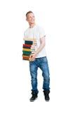Allievo che tiene una pila di libri Fotografia Stock