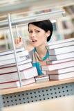 Allievo circondato con i libri nel panico Immagini Stock Libere da Diritti