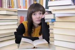 Allievo con i libri in una libreria Fotografie Stock Libere da Diritti