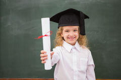 Allievo con il cappello e la tenuta di graduazione del suo diploma Fotografie Stock Libere da Diritti