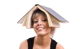 Allievo con il libro sulla sua testa Immagini Stock