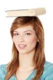 Allievo con il libro sulla sua testa Immagine Stock Libera da Diritti