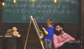 Allievo con l'insegnante alla scuola Il padre ed il figlio studiano la conoscenza nuova e le abilità Bambino che indica alla lava Fotografia Stock Libera da Diritti