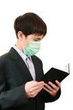 Allievo con un libro nella mascherina medica Fotografia Stock