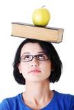 Allievo con una mela e libro sulla sua testa Fotografia Stock