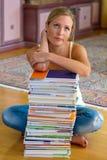 Allievo con una pila di libri e di calcolatori Fotografie Stock