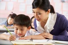 Allievo d'aiuto che lavora allo scrittorio a scuola cinese Immagini Stock