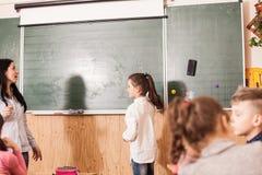 Allievo d'aiuto dell'insegnante alla lavagna Fotografia Stock