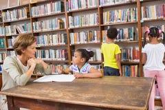 Allievo d'aiuto dell'insegnante in biblioteca Immagini Stock Libere da Diritti