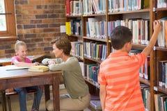 Allievo d'aiuto dell'insegnante in biblioteca Fotografia Stock Libera da Diritti