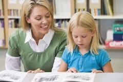 Allievo d'aiuto dell'insegnante con le abilità di lettura Immagini Stock
