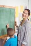 Allievo d'aiuto dell'insegnante grazioso alla lavagna Immagini Stock Libere da Diritti
