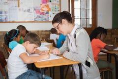 Allievo d'aiuto dell'insegnante grazioso in aula Immagine Stock Libera da Diritti