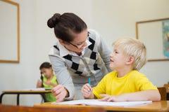 Allievo d'aiuto dell'insegnante grazioso in aula Immagine Stock