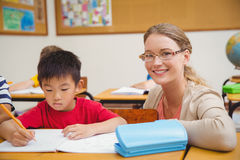 Allievo d'aiuto dell'insegnante grazioso in aula Fotografia Stock