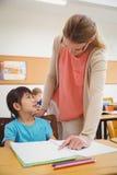 Allievo d'aiuto dell'insegnante grazioso in aula Immagini Stock
