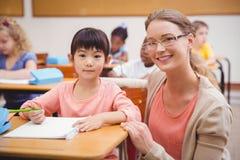 Allievo d'aiuto dell'insegnante grazioso in aula che sorride alla macchina fotografica Immagini Stock