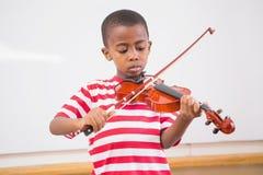 Allievo del fuoco che gioca violino in aula Fotografia Stock