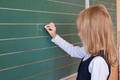 Allievo del primo grado una scrittura della ragazza sulla lavagna verde alla lezione della scuola Fotografia Stock