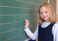 Allievo del primo grado una scrittura della ragazza sulla lavagna verde alla lezione della scuola Immagine Stock