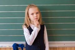 Allievo del primo grado una scrittura della ragazza sulla lavagna verde alla lezione della scuola Fotografie Stock