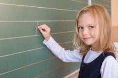 Allievo del primo grado una scrittura della ragazza sulla lavagna verde alla lezione della scuola Fotografia Stock Libera da Diritti
