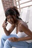 Allievo dell'afroamericano sul telefono delle cellule che guarda indietro Immagini Stock