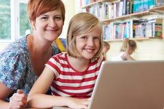 Allievo della scuola con l'insegnante Using Laptop Computer in aula Immagini Stock
