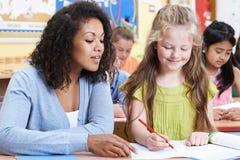Allievo della scuola di With Female Elementary dell'insegnante nella classe Immagine Stock