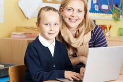 Allievo della scuola di Helping Female Elementary dell'insegnante nella classe del computer Immagini Stock