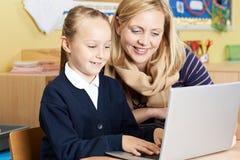 Allievo della scuola di Helping Female Elementary dell'insegnante nella classe del computer Fotografia Stock