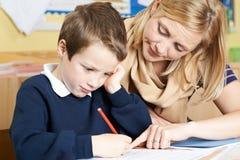 Allievo della scuola di Helping Male Elementary dell'insegnante con il problema Immagine Stock Libera da Diritti