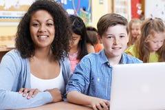 Allievo di Helping Male Elementary dell'insegnante nella classe del computer Fotografia Stock Libera da Diritti