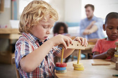 Allievo di Montessori che lavora allo scrittorio con le forme di legno Immagine Stock