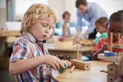 Allievo di Montessori che lavora allo scrittorio con le forme di legno Fotografia Stock