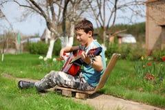 Allievo di musica che gioca la chitarra Fotografia Stock